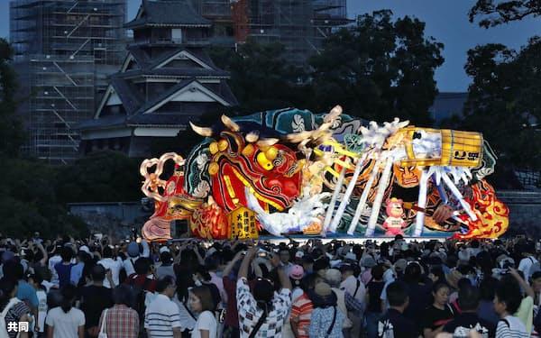 熊本地震からの復興を願い、「ラッセラー」の掛け声とともに熊本城二の丸広場を練り歩く青森の大型ねぶた。後方は修復中の熊本城(2日夕)=共同
