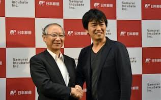 握手する日本郵便の福田聖輝副社長(左)とサムライインキュベートの榊原健太郎社長