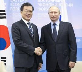 6日、ウラジオストクでの会談を前に握手するロシアのプーチン大統領(右)と韓国の文在寅大統領=聯合・共同