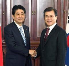 会談前に韓国の文在寅大統領(右)と握手する安倍首相=7日、ウラジオストク(共同)