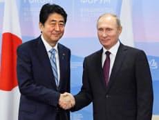 会談前に握手するロシアのプーチン大統領(右)と安倍首相(7日、ウラジオストク)=共同