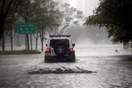 10日、フロリダ州マイアミで洪水の道路を走行する車=ロイター