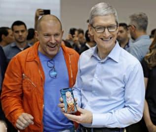 新型iPhoneを手にするアップルのティム・クック最高経営責任者(CEO)=右(ロイター)