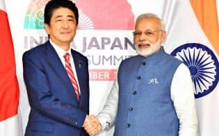 インドのモディ首相(右)との会談を前に握手する安倍首相(14日、インド・ガンディナガル)=代表撮影・共同