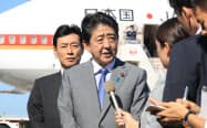 ニューヨークへの出発を前に記者の質問に答える安倍首相(18日午後、羽田空港)