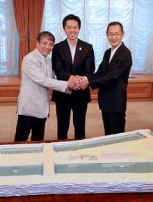 模型を前に握手する(左から)安藤氏、吉村市長、山中教授(19日午前、大阪市北区)