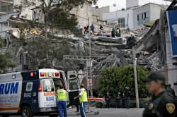 19日、崩壊した建物で救助活動する人たち(メキシコシティ)=AP