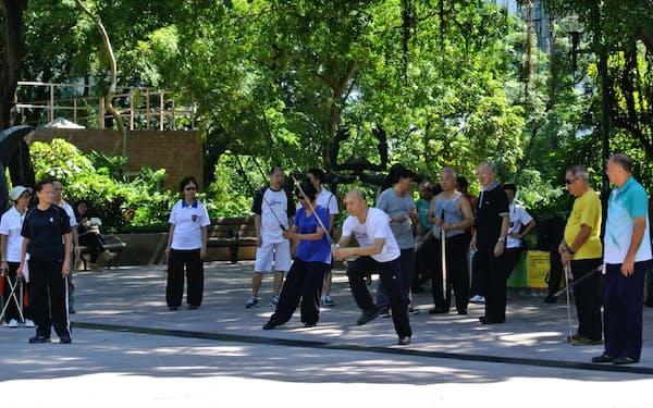香港の公園で、剣術を学ぶ人たちが師匠の動きを見つめている。広場は体を動かす場になっている