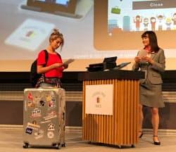外国人女性が旅行客にふんして荷物を預けるシーンなどを演じた(21日、東京都内)