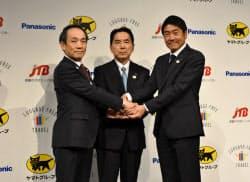 記者会見で手を握り合うJTBの古野浩樹執行役員(左)ら(21日、東京都内)