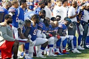 国歌斉唱時に起立せず抗議を表明するNFLの選手ら(24日、ニューヨーク)=AP