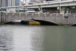 船体を低くして堂島川の大江橋の下を通過する一本松海運のクルーズ船
