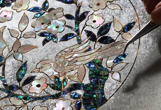 和紙に貝殻の真珠層を丁寧に貼っていく。完成後、糸状に裁断し生地に織り込む