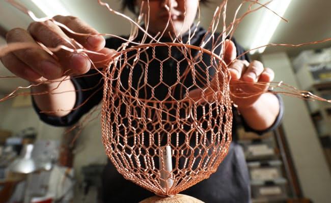 立体的に編み上げ、銅のリングを取り付ける