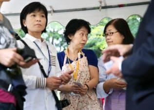 地域の祭り会場を訪れた立候補予定者の話を聞く有権者ら(1日、東京都内)