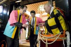 お水汲みで竹筒の護符に早春の若水をいただく鳥井副会長(左)=2014年