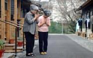 九州北部の豪雨から3カ月となり、仮設住宅前で手を合わせる入居者の女性(5日午前、福岡県朝倉市)=共同