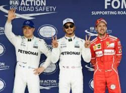 ポールポジションを獲得し、ポーズをとるルイス・ハミルトン。左は2番手のバルテリ・ボッタス、右は3番手のセバスチャン・フェテル(7日、鈴鹿サーキット)=共同