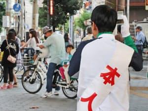 「本人」と書かれたたすきをかけて街頭演説する衆院選立候補予定者(8日、大阪市)