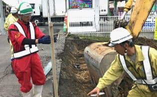 道路舗装の工事現場で率先して働くベトナム人技能実習生のズオン・キム・ナムさん(左、旭川市)