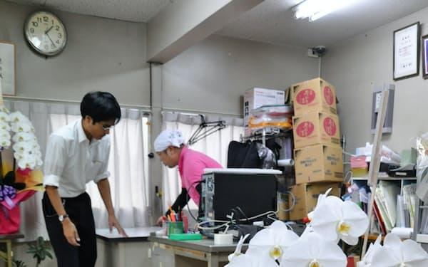 選挙事務所が片付けに追われるなか、当選を祝う花が届けられていた(23日、名古屋市)