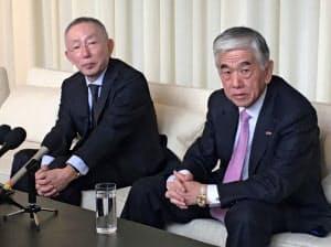 24日、ニューヨーク市内で会見するファストリの柳井氏(左)と東レの日覚昭広社長