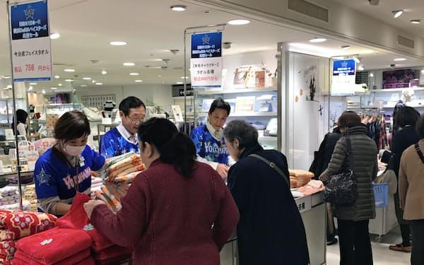 店員がベイスターズのユニホームを着てセールを盛り上げる(25日、高島屋横浜店)
