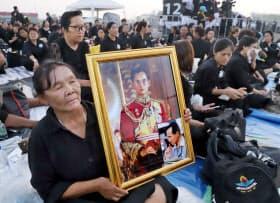 タイのプミポン前国王の火葬式で、写真を掲げ葬列の到着を待つ人たち(26日、バンコク)=沢井慎也撮影