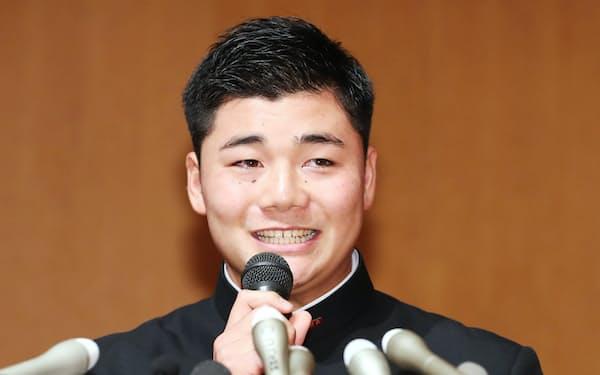 日本ハムが交渉権を獲得し、記者会見で笑顔を見せる早実高の清宮幸太郎選手(26日午後、東京都国分寺市)