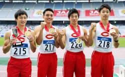 男子400メートルリレーで優勝し、メダルを手にする中央大の(左から)川上、竹田、大久保、染谷(28日、日産スタジアム)=共同