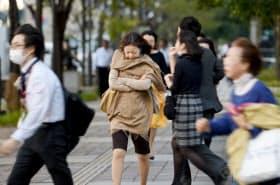冷たい風を受けながら歩く人たち(30日午前、東京・丸の内)