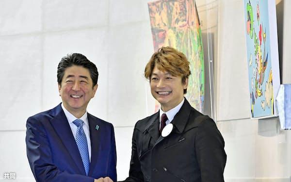 障害者らの作品が展示されたアート展を鑑賞し、案内役の香取慎吾さん(右)と握手する安倍首相(30日午前、東京都港区)=共同