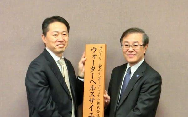 講座の看板を持つサントリー食品の西本正三執行役員(左)と弘前大の佐藤敬学長(1日、弘前大)