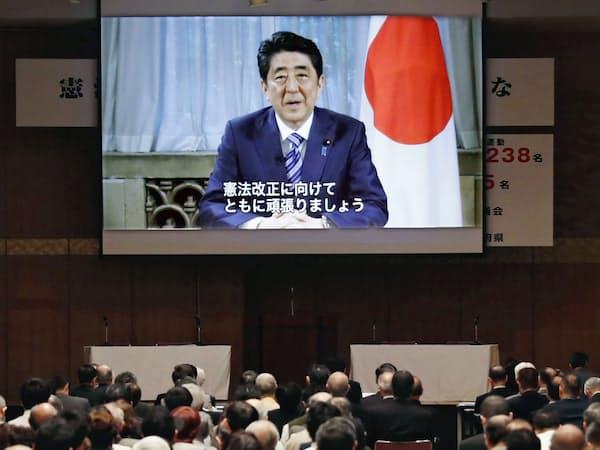 首相は2020年の新憲法施行目標を5月にビデオメッセージで表明した(東京都千代田区で開いた改憲を訴える会合で)=共同