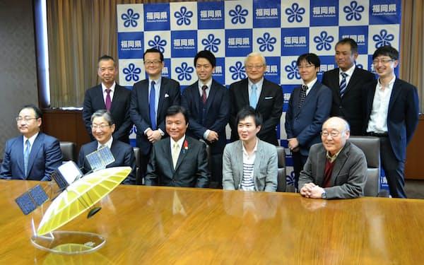 衛星の模型を前に福岡県庁で会見した小川洋福岡県知事(前段中央)とQPS研究所の大西俊輔社長(前段右から2人目)ら
