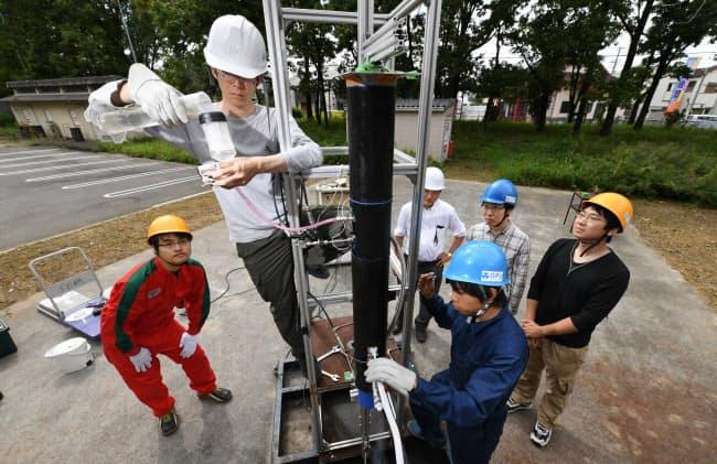 ロケットエンジン噴射実験の準備をする学生ら。湯で液体窒素を気化させ噴き出したガスを推進力にする(堺市の大阪府立大学)
