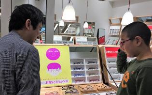 店頭で近視抑制のバイオレットライトを透過させるレンズを試す小学生