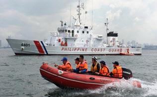 フィリピンの海上警備員にゴムボートの操縦を指導する日本の海上保安官(後ろから3人目)。後方は日本が供与した新造巡視船(海上保安庁提供)