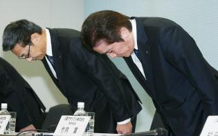 記者会見で頭を下げる三菱マテリアルの竹内章社長(右)ら(24日午後、東京都千代田区)