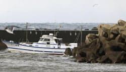 漂着した木造船がなくなった防波堤付近の海。船から秋田県警の警察官が確認していた=25日午前、秋田県由利本荘市