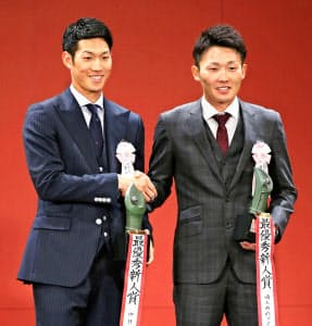 新人王に選ばれ、笑顔で握手する中日の京田陽太(左)と西武の源田壮亮=共同