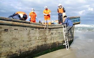 国籍不明の木造船を調べる関係者(27日午前、秋田県男鹿市 同市提供)=共同