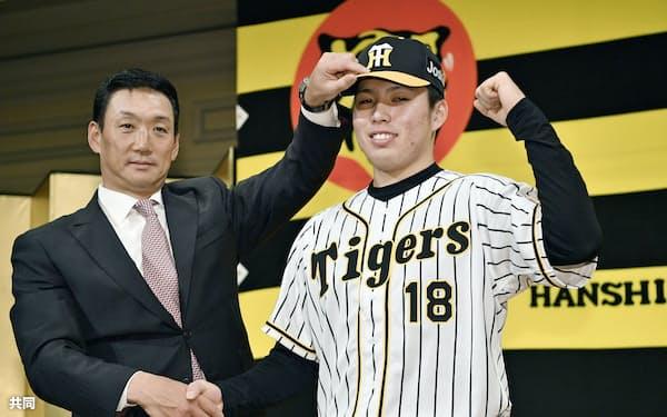 阪神の新入団選手発表で金本監督(左)とポーズをとるドラフト1位指名の馬場皐輔投手(4日、大阪市内のホテル)=共同