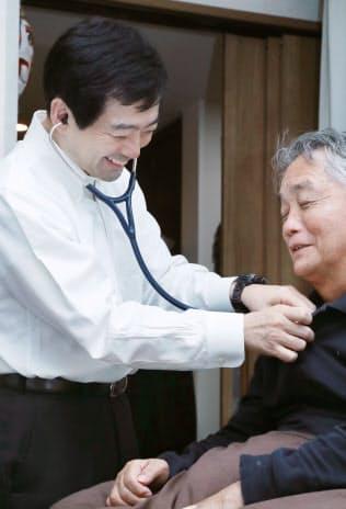 患者宅で訪問診療する武藤医師(東京都豊島区)