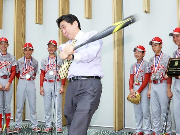 首相官邸を訪れたリトルリーグ世界選手権優勝チームの前で素振りを披露する安倍首相(11日午後)