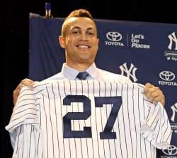 ヤンキースへの移籍が決まり、新しいユニホームを手にするジアンカルロ・スタントン外野手(11日、オーランド)=MLB提供ゲッティ共同