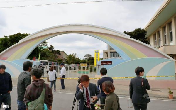 米軍ヘリの一部が落下し、報道陣が集まる沖縄県宜野湾市立普天間第二小学校前(13日午前)=共同