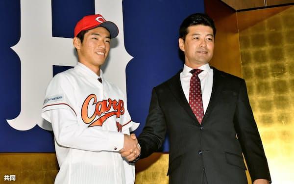 広島の新入団記者会見で、緒方監督(右)と握手をするドラフト1位の中村奨成捕手(13日、広島市)=共同