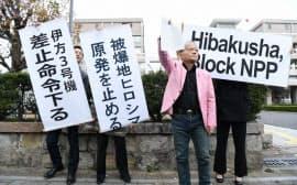 伊方原発3号機運転差し止めの仮処分が決定し、広島高裁前で垂れ幕を掲げる住民側(13日午後、広島市中区)