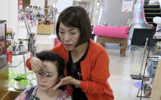 美顔器を試す訪日観光客(9月、米子高島屋)